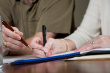 stock-photo-11173640-closeup-of-pens-and-paper-while-business-people-discuss-reports[1]